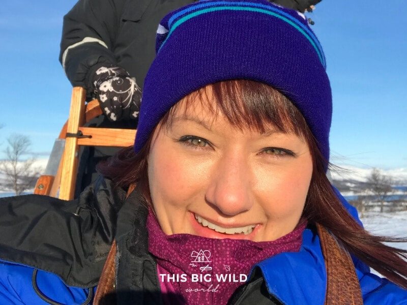 Close up of my face with the sun shining on it because I forgot my sunglasses. I am riding in the sled and another person is behind me driving the sled.