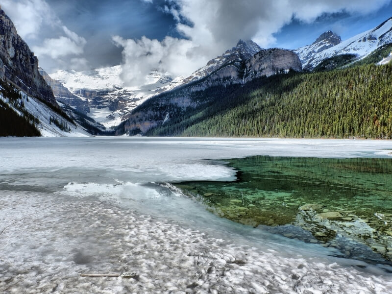 The bright blue green water of Lake Louise peeks through a coating of ice at the base of the snow-covered Canadian Rockies in Banff National Park.