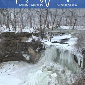 Text: Frozen Waterfalls Minneapolis Minnesota Image: Water flows under a bridge and down a waterfall that is mostly frozen creating a large icicle into a frozen pool. Surrounding the waterfall is a forest covered in a perfect dusting of snow.