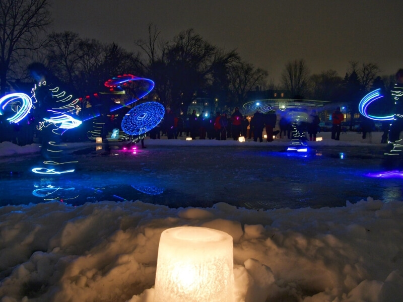 A candle holder formed out of ice is lit and sitting on snow in the foreground. Behind the candle a number of dancers are ice skating holding blue and red lights at nighttime on Lake of the Isles in Minneapolis during the Luminary Loppet annual event.
