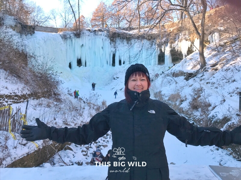 In the foreground, I am bundled up in black winter clothes with just my face showing. Behind me is a completely frozen Minnehaha Falls in Minneapolis.