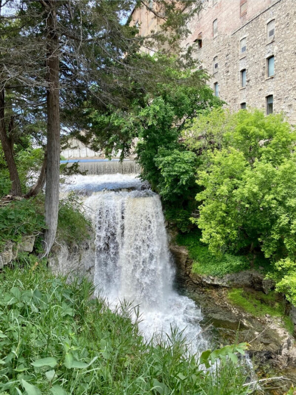 Vermillion Falls flowing rapidly along an old brick building in downtown Hastings Minnesota. Both sides are lines with lush green trees and shrubs.  Photo Credit: Expedition Kristen