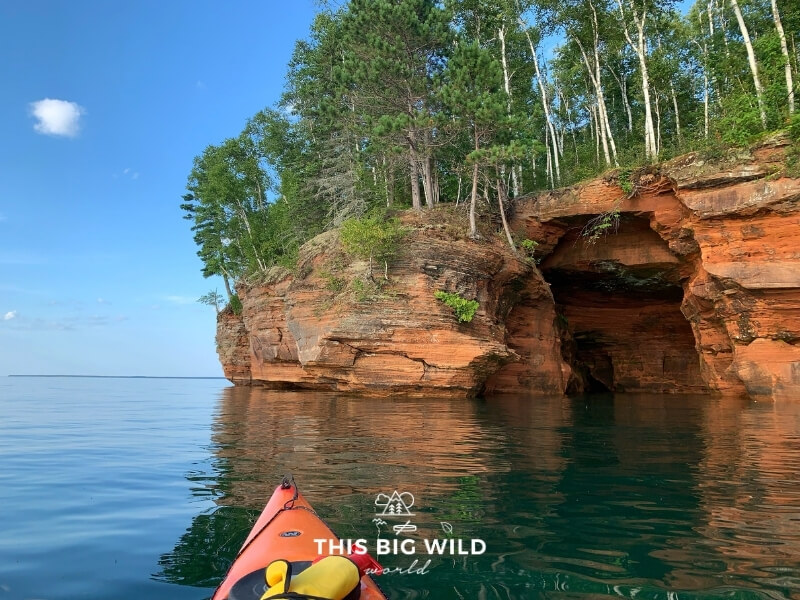Bright red rocks of the Apostle Islands National Lakeshore near Bayfield Wisconsin as seen from inside of a kayak on Lake Superior.