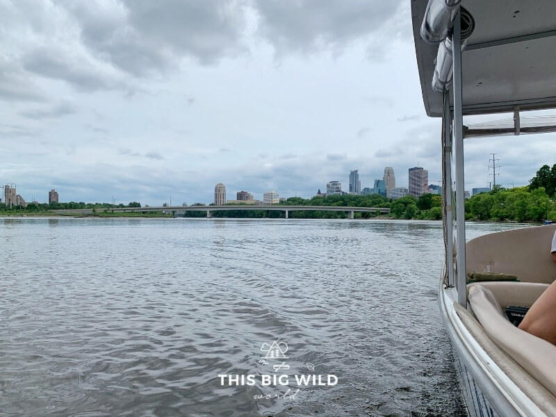A partial view of the Minneapolis skyline is visible from the Minneapolis Water Taxi as it glides through the Mississippi River on a cloudy day.