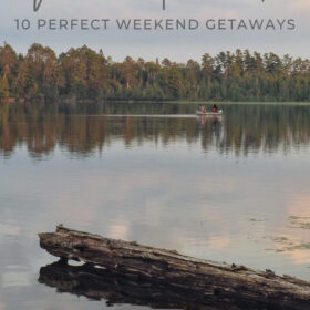 Text: Minnesota Road Trips - 10 perfect weekend getaways Image: A single canoe is paddled across a lake with a line of trees in the distance and a log sticking out of the water in the foreground. The sun is setting giving everything a pink hue.