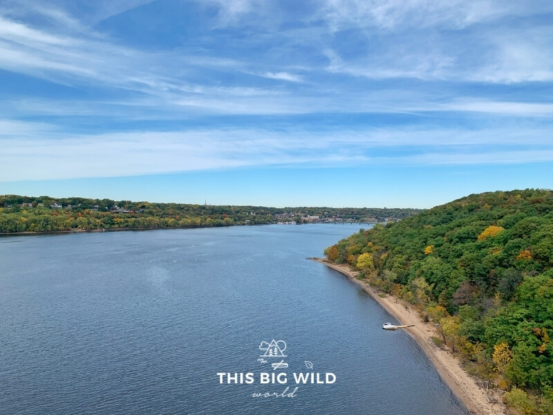The St Croix River in summertime with bright green forest on either side. On the left is Stillwater in Minnesota and on the right is Wisconsin.