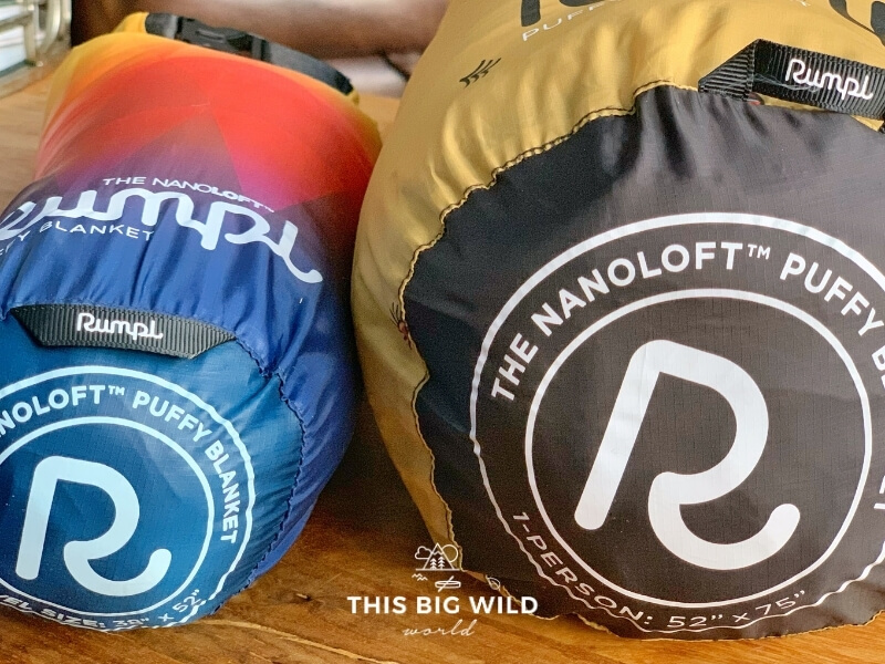 The ends of two Rumpl Nanoloft blanket stuff sacks laying side by side on a wooden surface.