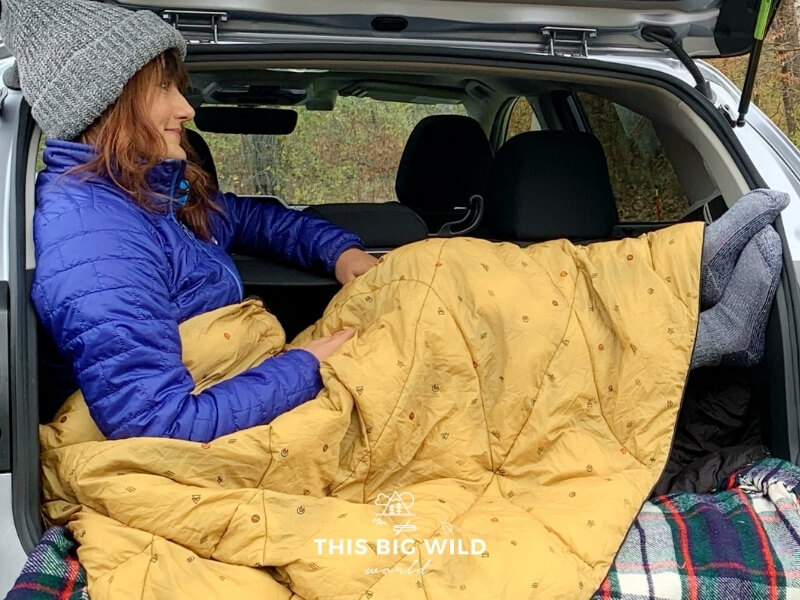 Me sitting in the back of my vehicle while car camping in the fall. Wearing a gray hat, blue jacket and a golden Rumpl Nanoloft blanket over my legs.