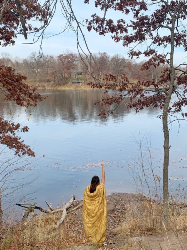 Me standing on the edge of a lake in fall wearing a golden Rumpl Nanoloft blanket as a cape with one fist raised in the air.