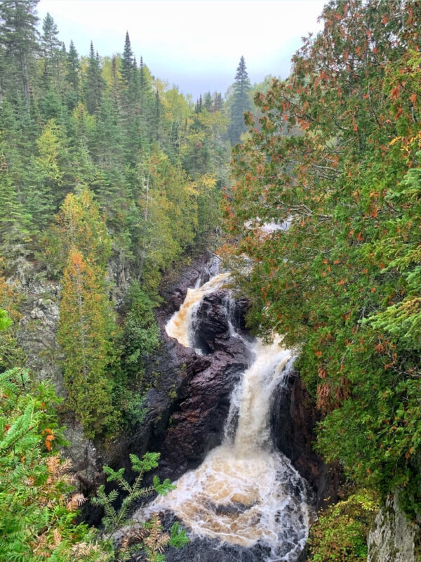 A waterfall cascades down three levels of dark brown rock as seen through a forest of tall trees just starting to change colors in autumn. It's a foggy and misty day with a slight haze. Devil's Kettle Falls at Judge C.R. Magney State Park in Minnesota.