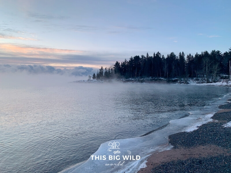 A low fog hangs over the water along the icy shore of Lake Superior at sunrise in winter.