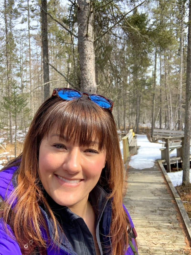 A close up of me with a smile on a warm sunny day at the end of winter in Mille Lacs Kathio State Park in Minnesota. Behind me is a boardwalk over a bog in the forest, covered in snow.