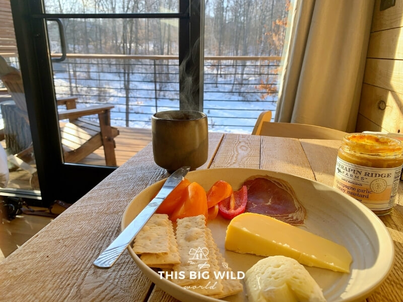 A charcuterie and cheese plate with locally sourced mustard and a steaming cup of coffee on a wood table looking out onto the patio at Cuyuna Cove.