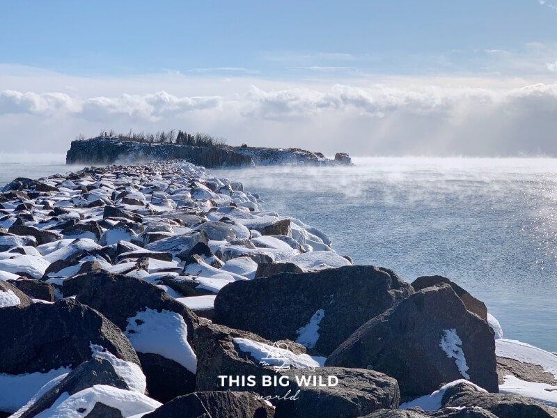 Snow covered rocks stretch out into Lake Superior towards Pellet Island on a sunny winter day. A low fog hangs over the water.