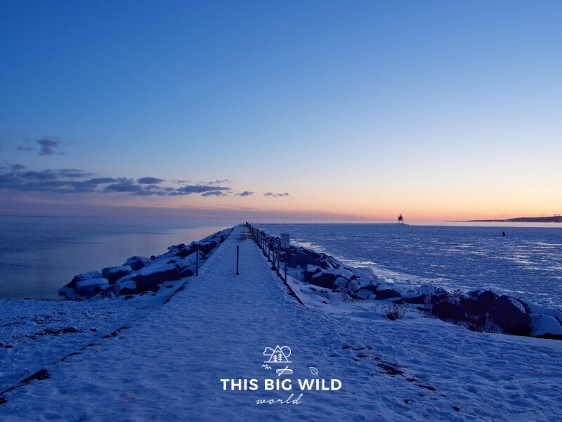 Sunset at Two Harbors Minnesota lighthouse on Lake Superior in winter. The Lakeshore is covered in ice and the sky is bright pink and blue.