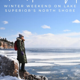 Text: Two Harbors MN, winter weekend on lake superior's north shore Image: Me in puffy green jacket and gray hat standing on an icy rock along the rugged shoreline of Lake Superior in winter