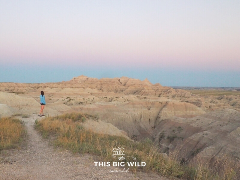 Me wearing a lightweight long sleeve blue top with black shorts at sunset in Badlands National Park in summer.
