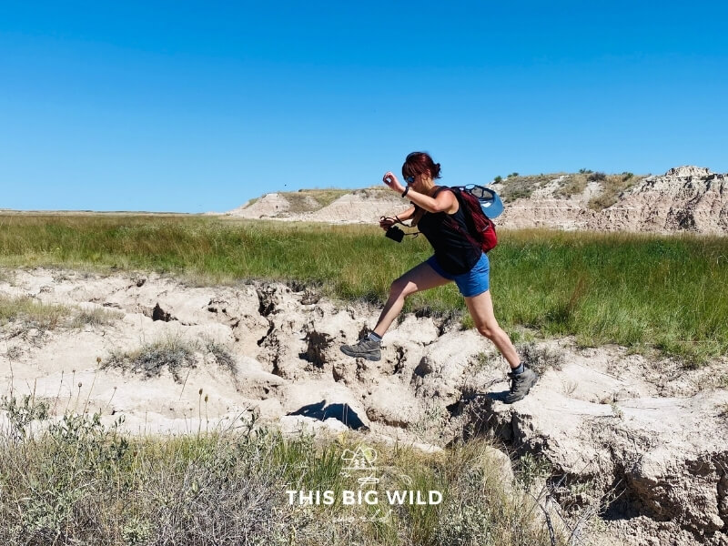 Me wearing a flowy black breathable tank top and blue breathable shorts while jumping across a washed out trail in the Badlands.