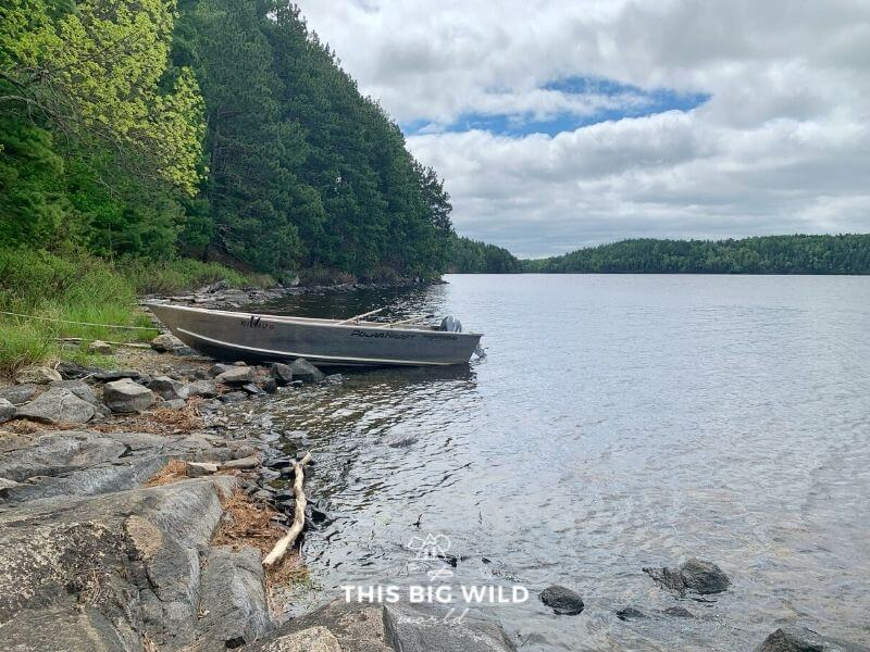 A motorized fishing boat is parked on a rocky shoreline in Voyageurs National Park.