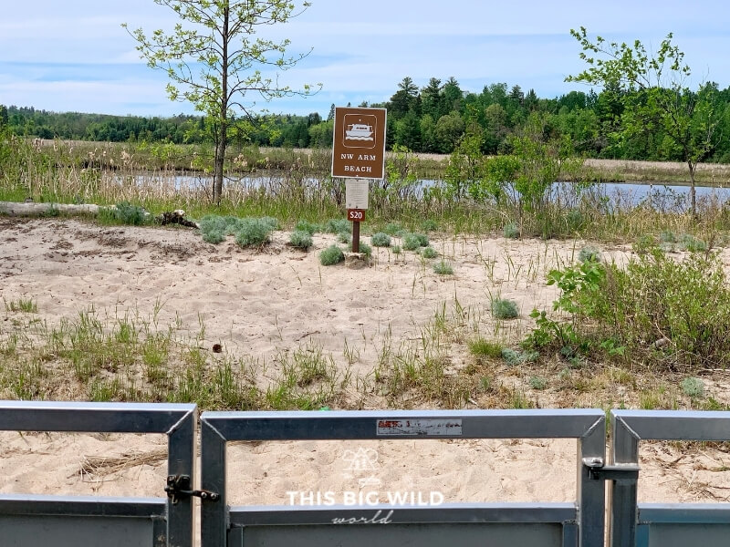 A brown rectangular sign with a houseboat symbol on a beach in Voyageurs National Park in Minnesota, designates a houseboat site.
