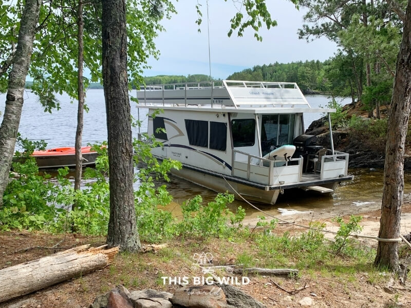 A houseboat is parked on a small stretch of sand surrounded on both sides by a rock.