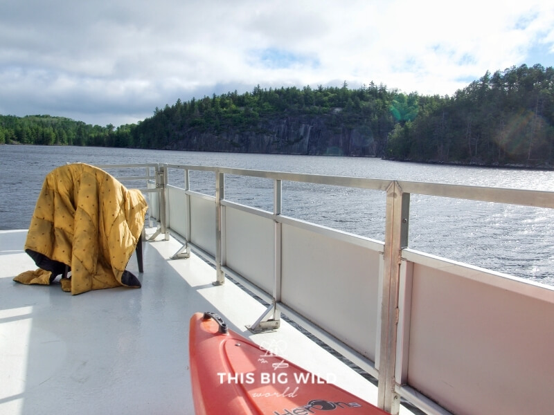 Yellow Rumpl nanoloft blanket is draped over a chair on the upper deck of a houseboat in Voyageurs National Park.