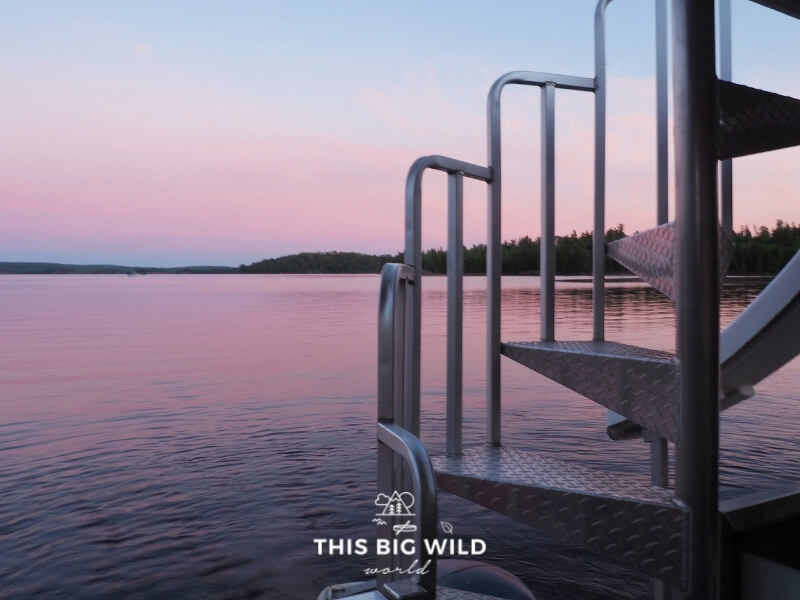 A bright pink sky as seen behind the stairs to the rooftop on a houseboat in Voyageurs National Park.