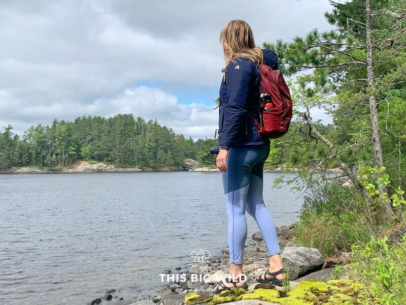 Me standing on the shoreline in water sandals, blue leggings, a warm jacket and red backpack.