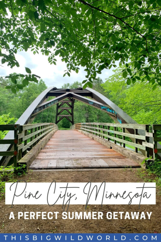 Text: Pine City, Minnesota - A Perfect Summer Getaway Image: A metal and wood bridge appears hidden in a forest on a cloudy day.