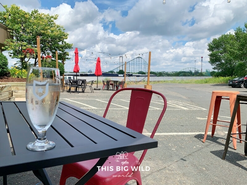 A glass of Badger Hill Brewing's hard seltzer on a table with a view of Valleyfair's roller coasters in the distance.