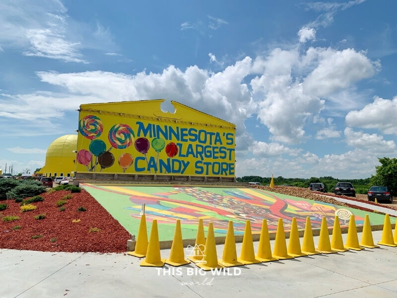 Big yellow sign for Minnesota's Largest Candy Store with a mural painted on the ground in front of it.