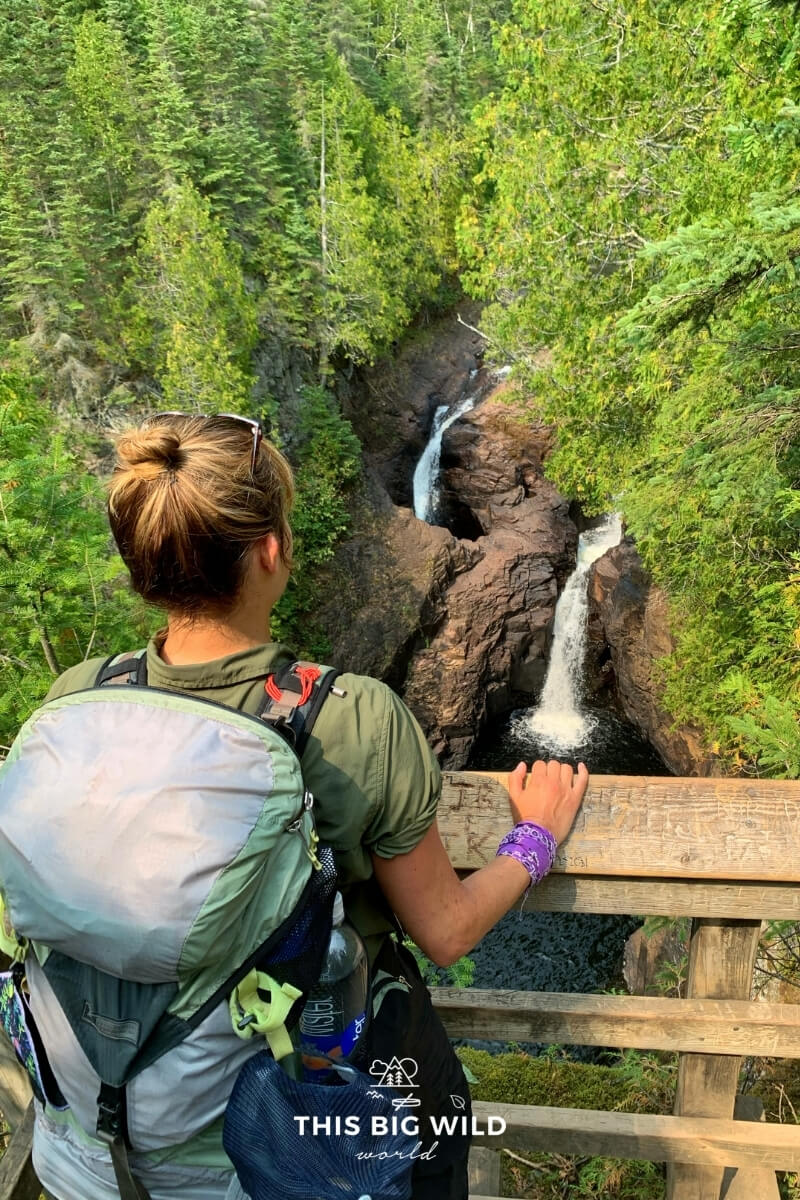 A woman is wearing a backpack while looking over a wooden railing towards a double waterfall along the Superior Hiking Trail.
