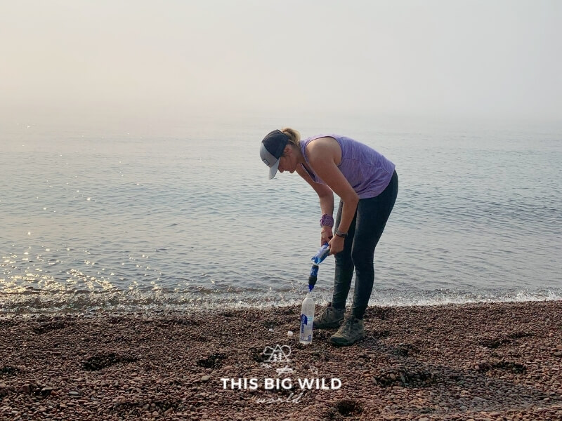 A woman is filtering water with a Sawyer Squeeze filter into a water bottle along the shore of Lake Superior in Minnesota.