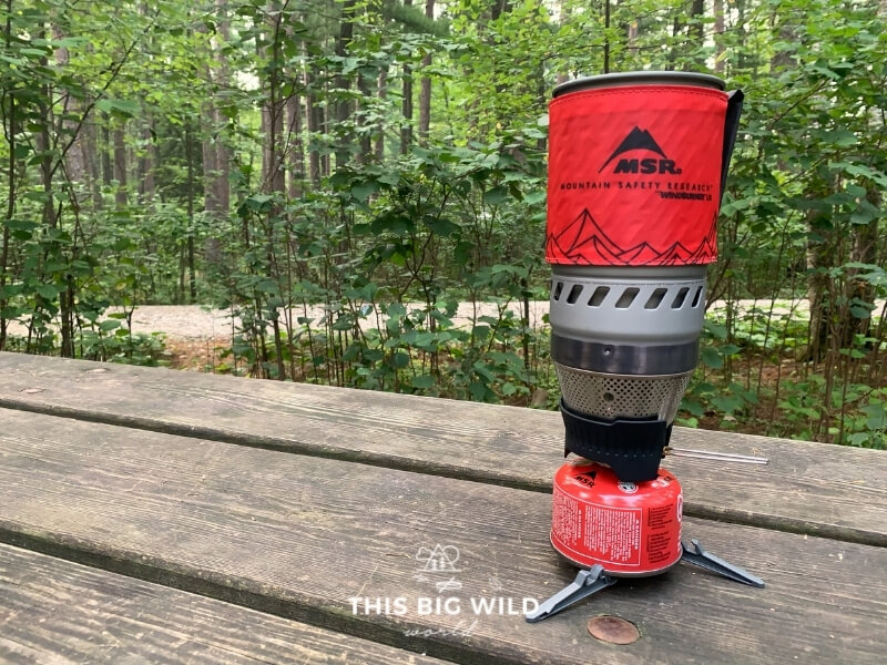 The MSR Windburner backpacking stove sits on a wooden table fully assembled with a red insulated container and wind shield.