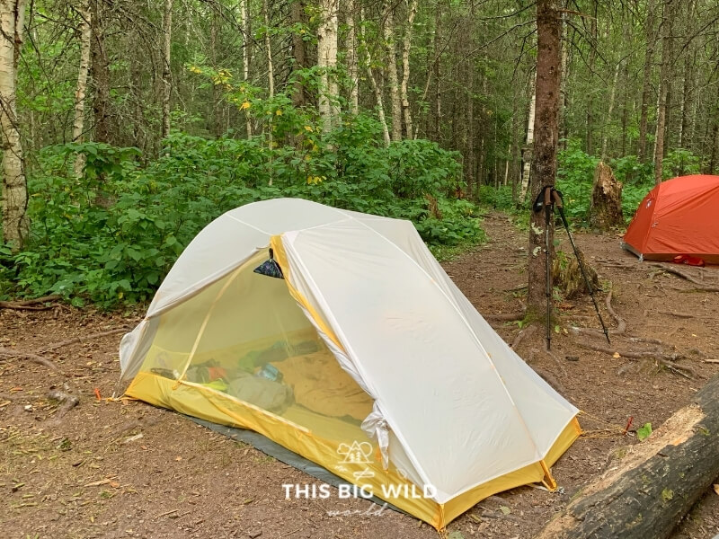 A yellow Big Agnes Tiger Wall tent has a gray rain fly over it at the North Little Brule River campsite on the Superior Hiking Trail.