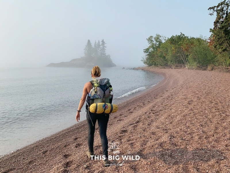 A woman walks away from the camera along Lake Superior on a foggy morning, carrying a backpack with a tent strapped securely at the bottom of it.